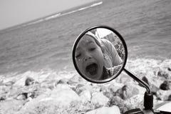 Reflexión de la familia en el espejo del ` s de la moto Foto de archivo libre de regalías