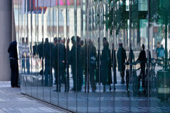 Reflexión de la gente en un edificio moderno foto de archivo