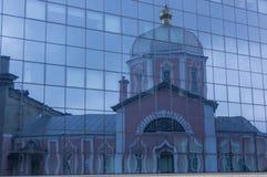 Reflexión de la iglesia en la fachada de cristal del edificio Fotos de archivo