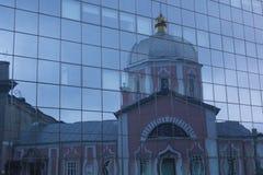Reflexión de la iglesia en la fachada de cristal del edificio Fotografía de archivo libre de regalías