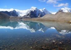 Reflexión de la montaña en el agua del lago con el cielo azul Foto de archivo