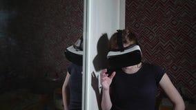 Reflexión de la muchacha en vidrios de VR en espejo metrajes