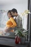 Reflexión de la mujer embarazada de abarcamiento del hombre Foto de archivo libre de regalías