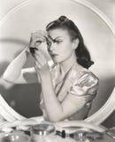 Reflexión de la mujer en el espejo que aplica maquillaje del ojo imagen de archivo