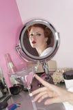Reflexión de la mujer hermosa en el espejo con el vidrio de martini en la tabla Imagen de archivo