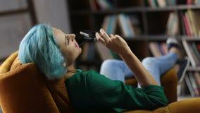 Reflexión de la mujer de moda que se relaja en silla acogedora metrajes