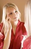 Reflexión de la mujer rubia joven que usa la crema Fotos de archivo
