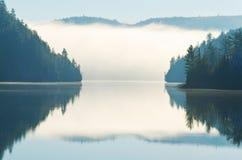 Reflexión de la niebla de la mañana que sube en el lago