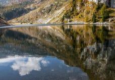 Reflexión de la nube en el lago de la montaña. Fotos de archivo libres de regalías