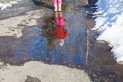 Reflexión de la pequeña muchacha en charco de la primavera foto de archivo