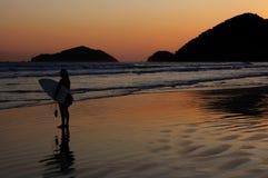Reflexión de la persona que practica surf y de la puesta del sol en una playa tropical Imagen de archivo