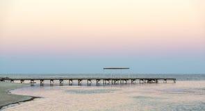 Reflexión de la puesta del sol con el embarcadero imagenes de archivo