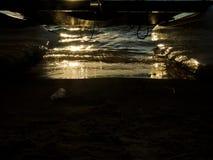 Reflexión de la puesta del sol en la arena mojada sobre una playa arenosa en el océano, debajo de un barco del tablero de resaca  imagen de archivo libre de regalías