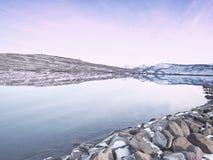 Reflexión de la puesta del sol en Heiðarvatn Seyðisfjörður Islandia foto de archivo libre de regalías