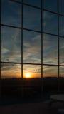 Reflexión de la puesta del sol en ventana grande del edificio Fotografía de archivo