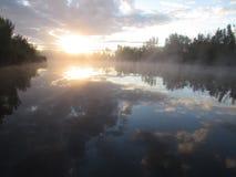 Reflexión de la salida del sol en el lago de la niebla de la mañana Foto de archivo libre de regalías