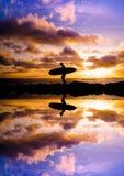 Reflexión de la silueta de la persona que practica surf de la puesta del sol Imagenes de archivo