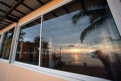 Reflexión de las escenas de la puesta del sol en la ventana del edificio Fotografía de archivo libre de regalías