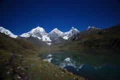 Reflexión de las montañas de la nieve en un lago azul Foto de archivo