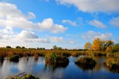 Reflexión de las nubes mullidas blancas en el agua azul del lago Fotografía de archivo libre de regalías