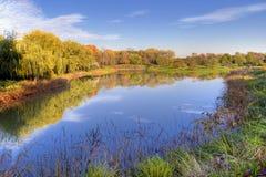Reflexión de los árboles y del cielo del otoño Imagen de archivo libre de regalías