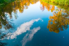 Reflexión de los árboles y del cielo, nubes del otoño en el río Foto de archivo