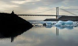 Reflexión de los cubos de hielo y del puente de ejecución con primero plano del hombre de la silueta en la laguna del glaciar de  Foto de archivo