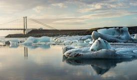 Reflexión de los cubos de hielo y del puente de ejecución en la laguna del glaciar de Jokulsarlon Foto de archivo libre de regalías