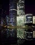 Reflexión de los edificios de oficinas de la defensa del La en la noche Imagenes de archivo
