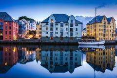 Reflexión de los edificios tradicionales y del barco en Alesund, la ciudad más hermosa de la costa occidental de Noruega fotografía de archivo