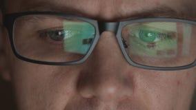 Reflexión de los sitios del movimiento en sentido vertical en lentes del hombre adulto joven en un cuarto oscuro almacen de video