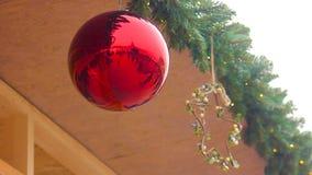 Reflexión de los transeúntes en la ejecución brillante de la bola de la Navidad debajo del tejado de la casa metrajes