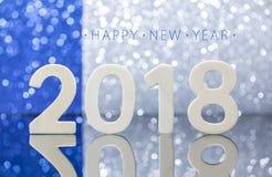 Reflexión de madera de los números del Año Nuevo 2018 en la tabla de cristal Fotos de archivo libres de regalías