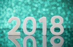 Reflexión de madera de los números del Año Nuevo 2018 en la tabla de cristal sobre verde Foto de archivo