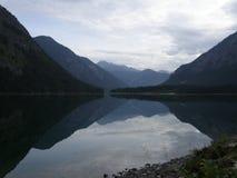Reflexión de montañas en el lago en la puesta del sol Fotos de archivo libres de regalías