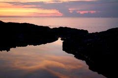 Reflexión de nubes en puesta del sol Fotografía de archivo