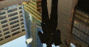 Reflexión de un hombre de negocios en el charco usando la tableta digital metrajes
