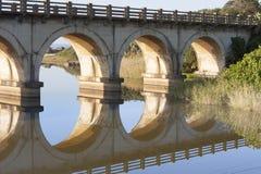 Reflexión de un puente ferroviario que cruza una laguna en la costa sur de KZN de Suráfrica Imagen de archivo