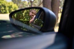 Reflexión del adolescente en el espejo de ala que se coloca al lado de un coche Fotografía de archivo