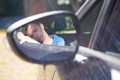 Reflexión del adolescente en espejo de ala que duerme en coche Imagen de archivo libre de regalías