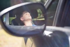 Reflexión del adolescente en espejo de ala que duerme en coche Imagen de archivo