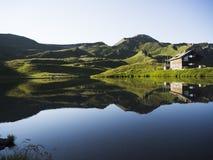 Reflexión del chalet y de la montaña en el lago foto de archivo libre de regalías
