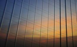 Reflexión del cielo de la puesta del sol en la pared del metal de la oficina Foto de archivo