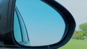 Reflexi?n del cielo en espejo de la vista posterior del lado derecho en la conducci?n de autom?viles almacen de metraje de vídeo