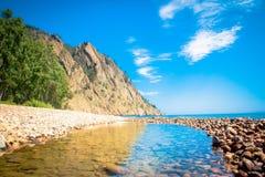 Reflexión del cielo en un charco en la orilla del lago Baikal fotografía de archivo libre de regalías