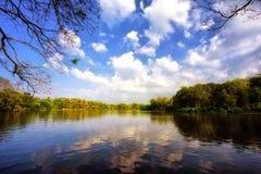 Reflexión del cielo y de las nubes en el lago Foto de archivo libre de regalías