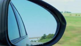 Reflexión del coche en espejo de la vista posterior del lado derecho durante la conducción metrajes