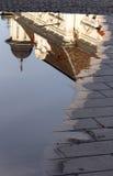 Reflexión del edificio viejo en el agua en el pavimento de la calle Imagen de archivo