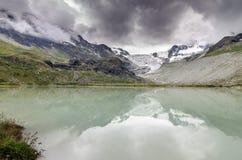 Reflexión del glaciar y del lago de Moiry con las nubes Imagen de archivo libre de regalías