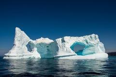 Reflexión del iceberg Pared grande con el arco y agua inmóvil imagen de archivo
